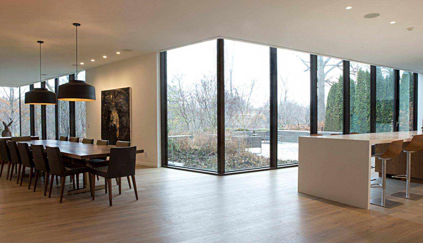 severnwoods-modern-rosedale-house-kitchen-and-dining-room-looking-into-backyard-through-glass-window-walls